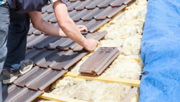 roof repair in birmingham and laying a tile on the battons of a roof